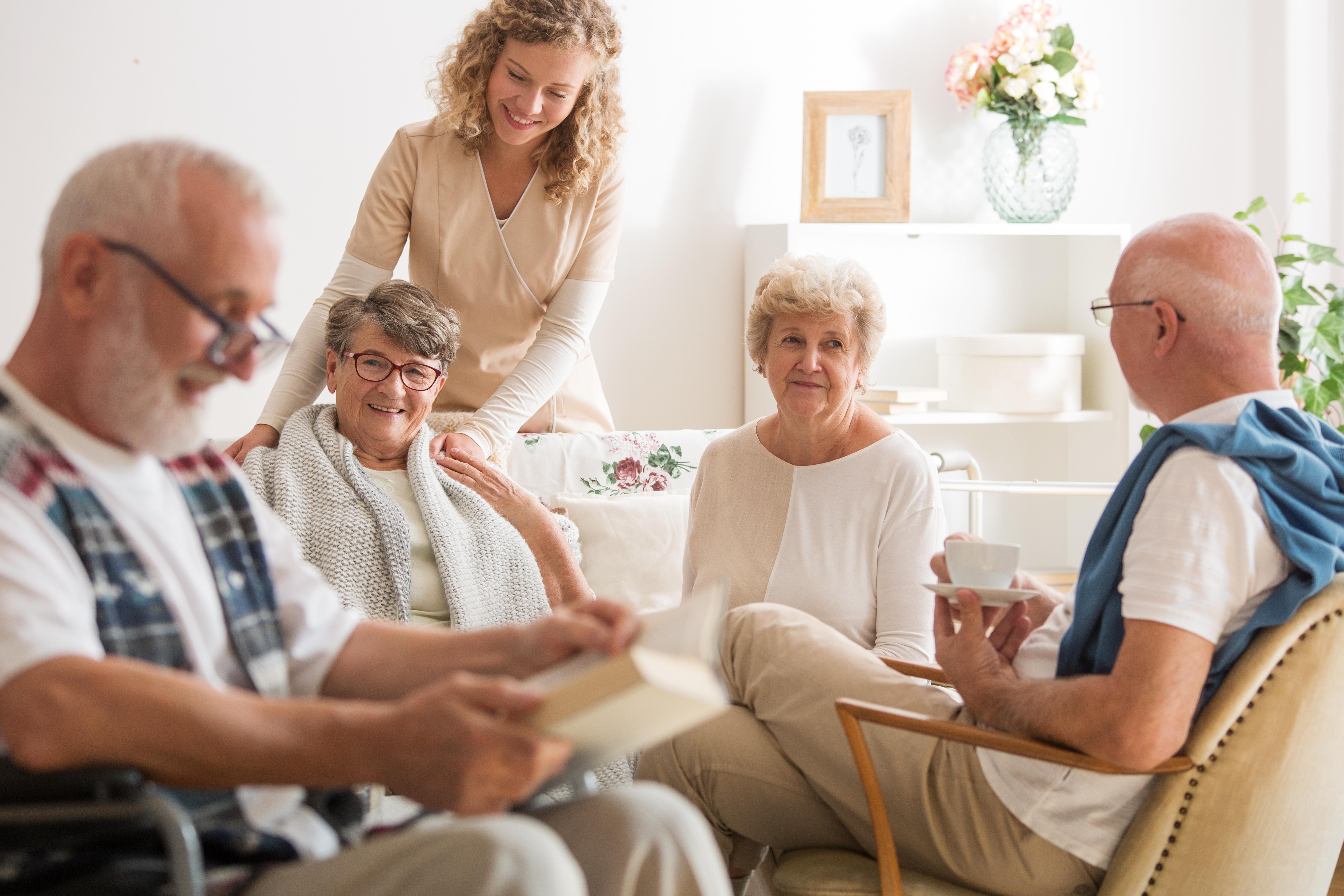 Group of senior friends sitting together at nursing home living room